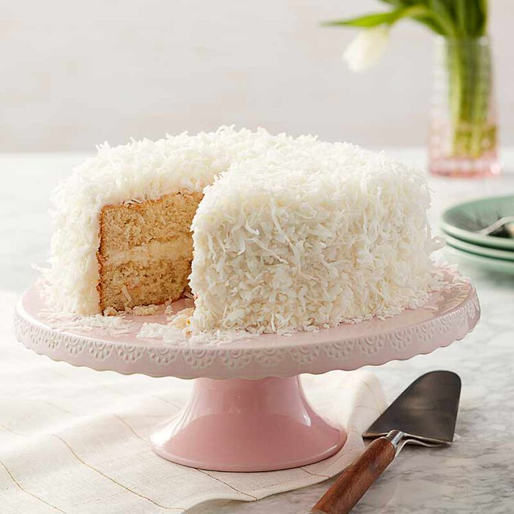 cake frosted with coconut buttercream frosting and coconut shreds