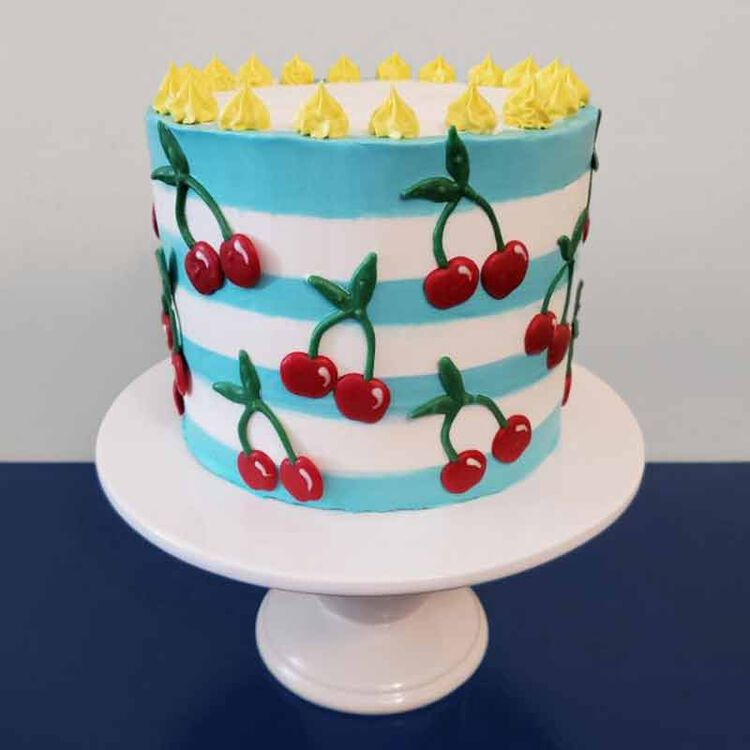 white, blue and yellow buttercream frosted cake decorated with cherries made out of candy melts candy