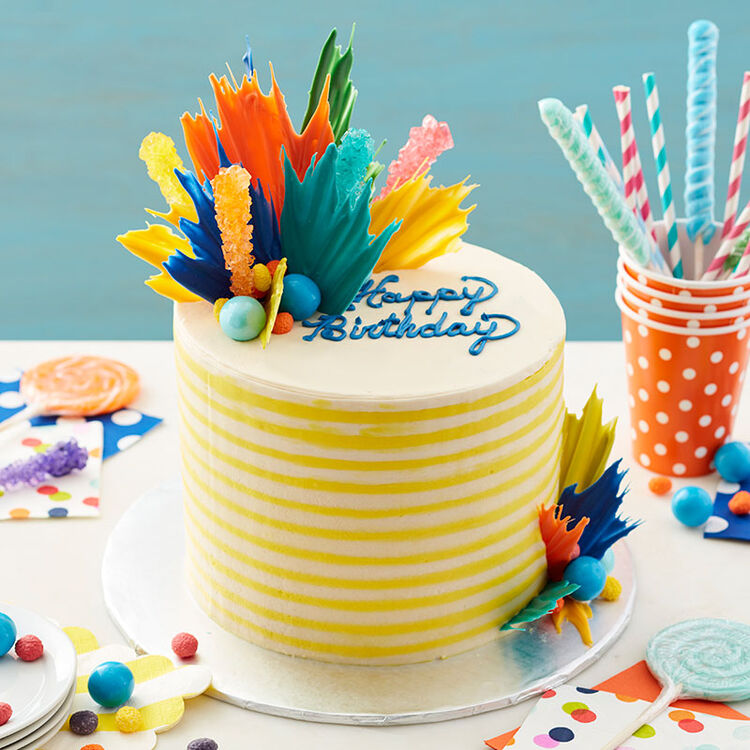 "White and yellow striped birthday cake topped with colorful ""exploding"" candy pieces and rock candy"