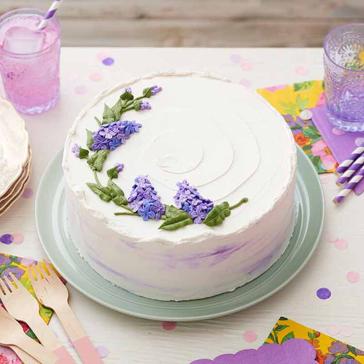 white buttercream frosted cake decorated with piped buttercream lilac flowers