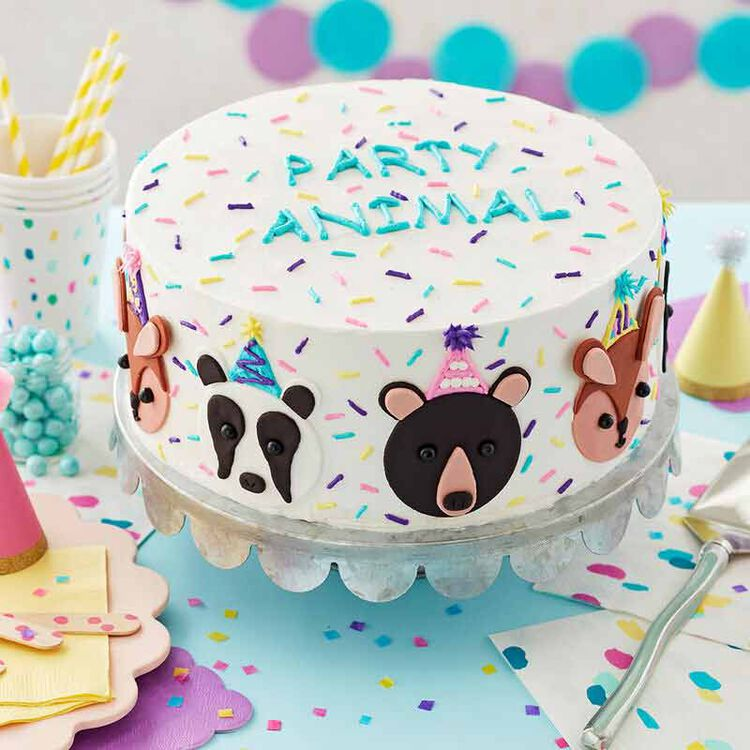 white buttercream frosted cake with blue writing that says party animal and animal decals around the cake