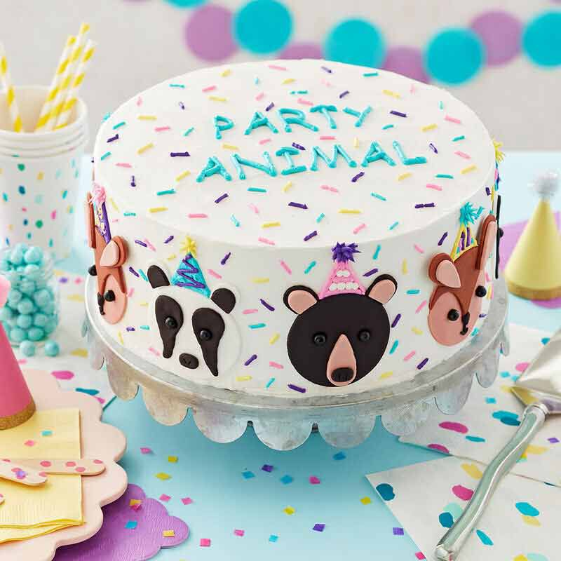 white buttercream frosted cake with blue writing that says party animal and animal decals around the cake image number 0