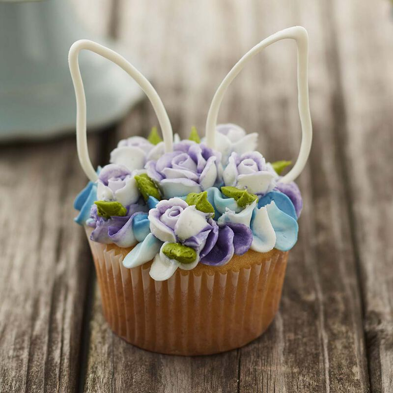 Blue and purple floral piped buttercream cupcakes with white candy easter bunny ears image number 1