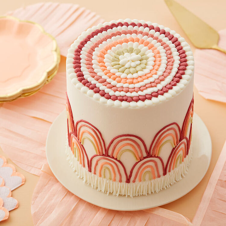White cake decorated with a rainbow in neutral colors around the sides and white fringe at the bottom