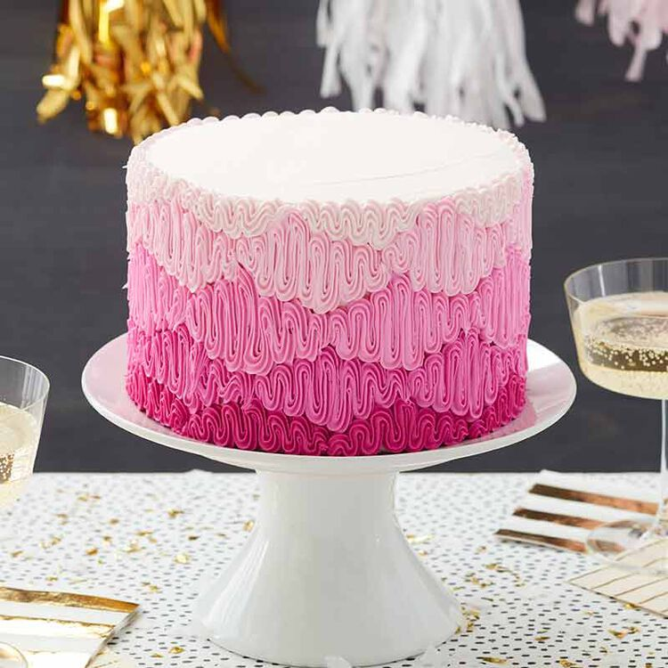 white buttercream frosted cake decorated with various shades of pink zig zag puffs