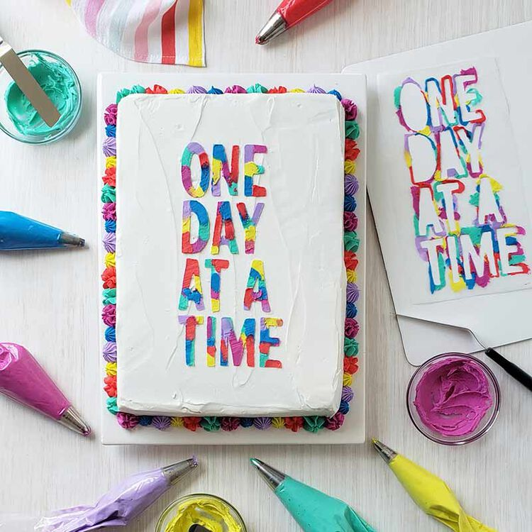 buttercream cake decorated with the words one day at a time in colorful buttercream
