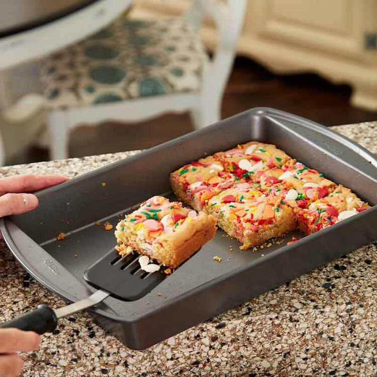 taking sugar cookie bars out of pan with a spatula