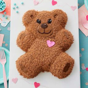 Adorable furry teddy bear shaped cake with pink heart on the chest