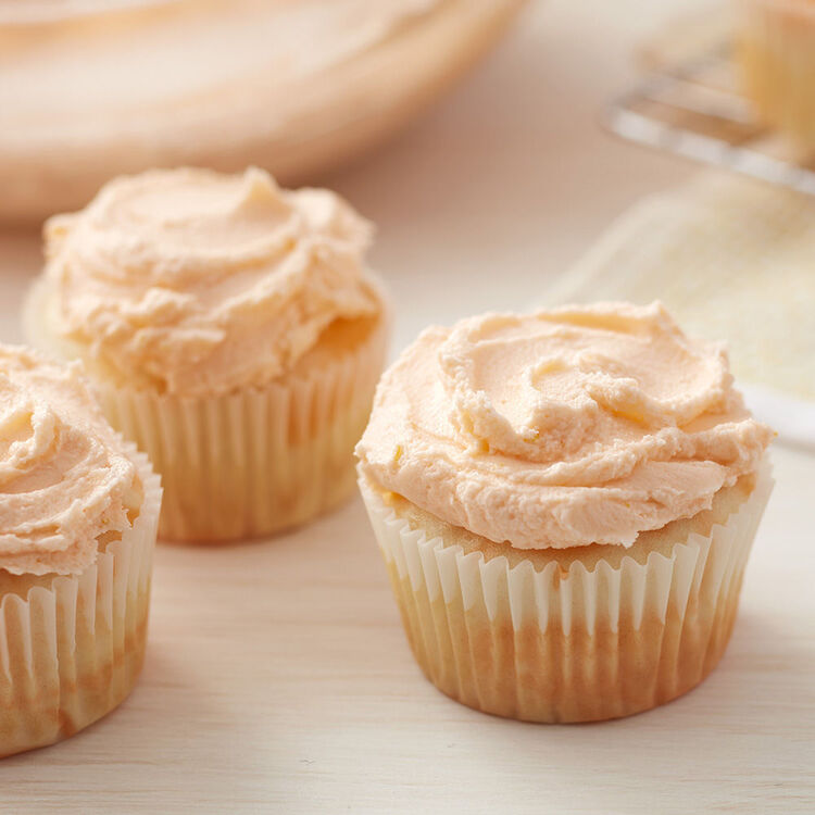 Close Up of Orange Buttercream Frosting on Vanilla Cupcakes