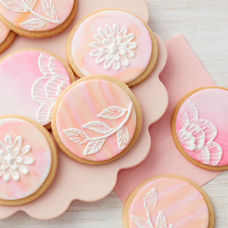 Round sugar cookies decorated with pink and yellow royal icing and piping gel to create an embroidered flowers look