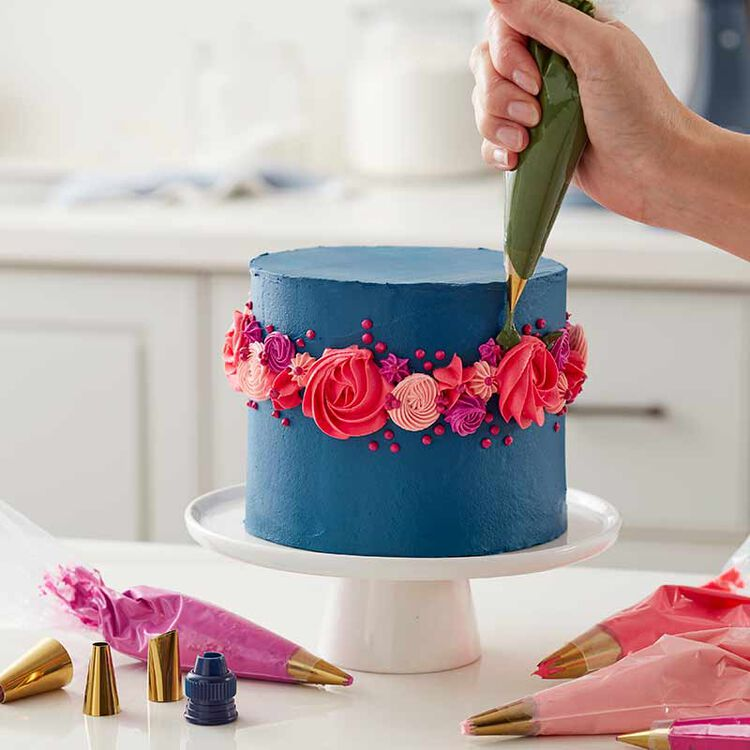 blue cake decorated with pink buttercream flowers