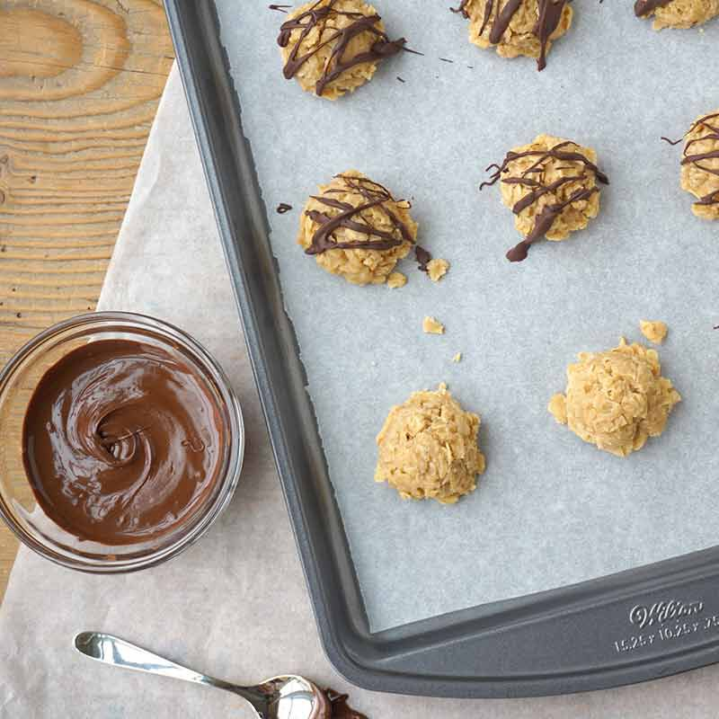 no bake peanut butter cookies with chocolate drizzle on a cookie sheet wit a bowl of chocolate candy melts next to the cookie sheet image number 1