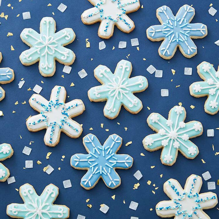 Blue background with snowflake cookies decorated with blue and white sprinkles.