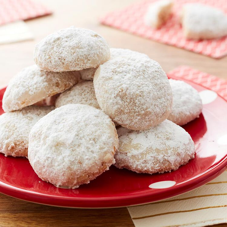 Pecan snowball cookies - round cookies covered in powdered sugar on a red plate