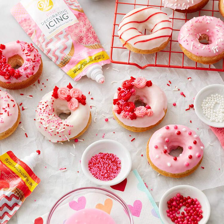 Doughnuts with pink and white icing and topped with a variety of pink, red, and white sprinkles in the process of being decorated