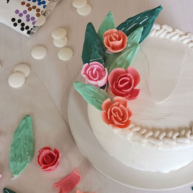 White buttercream cake with candy roses and leaves made using Candy Melts. Braided border around the top image number 1