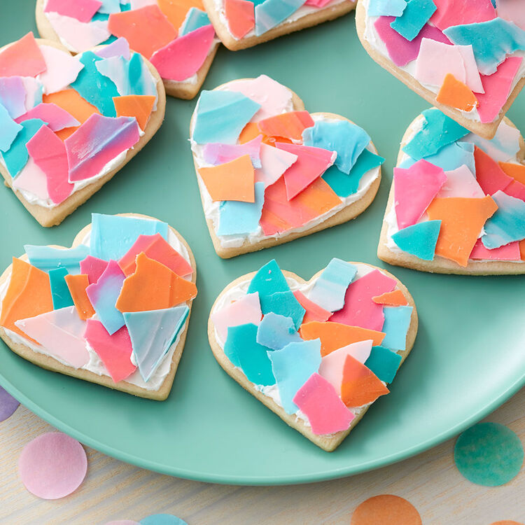 Plate of heart-shaped cookies topped with white icing and broken candy pieces made to look like confetti