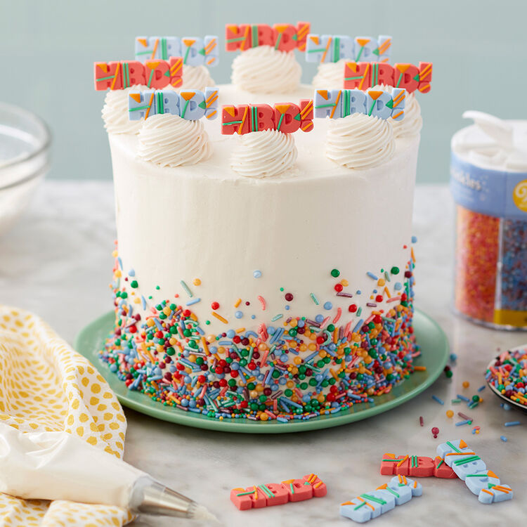 Happy Birthday Explosion Cake - Cake with sprinkles on the sides, and mounds of swirled frosting with HBD icing decs on top