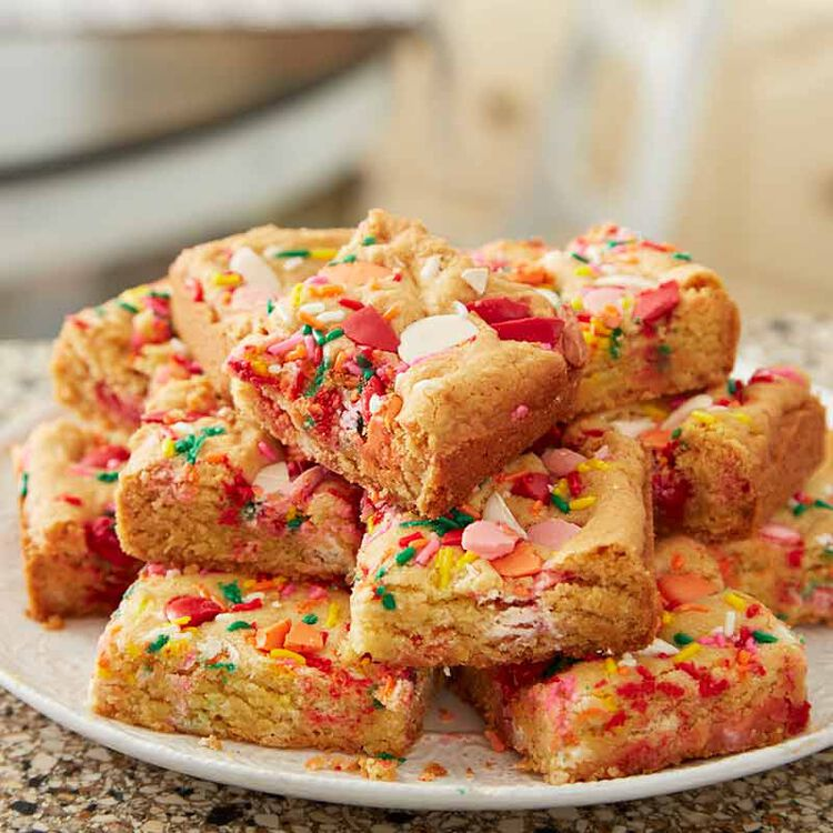 sugar cookie bars stacked on a plate
