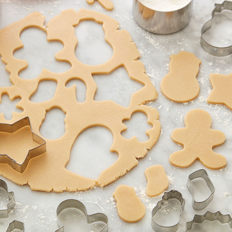 Roll-out butter cookie dough used to cut out holiday cookies with cookie cutters image number 0