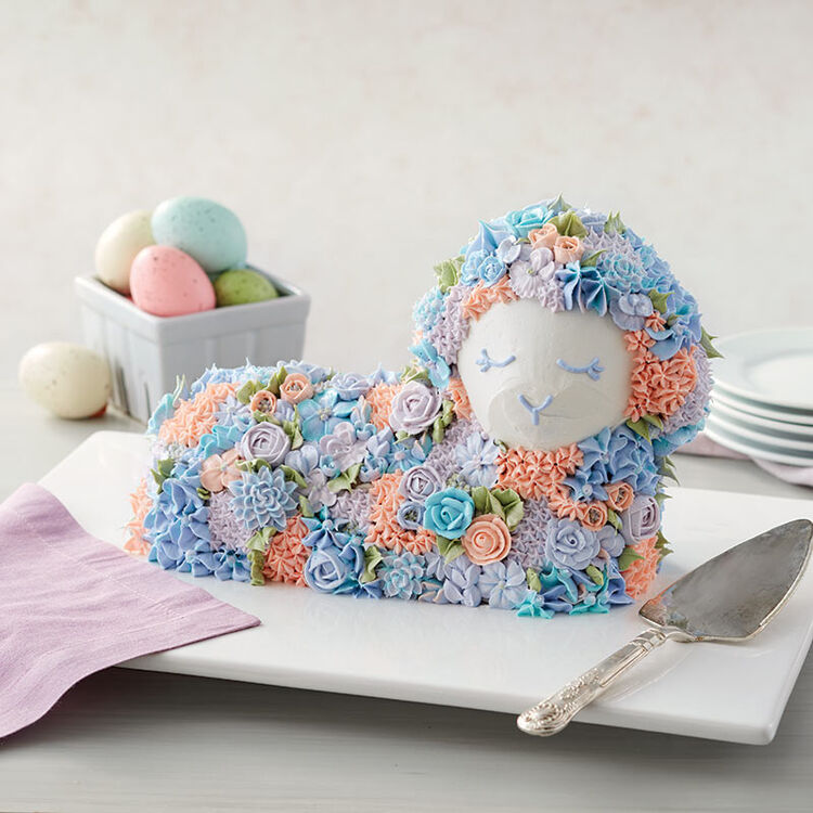 Easter 3-D lamb cake covered with blue, peach, and purple buttercream piped flowers