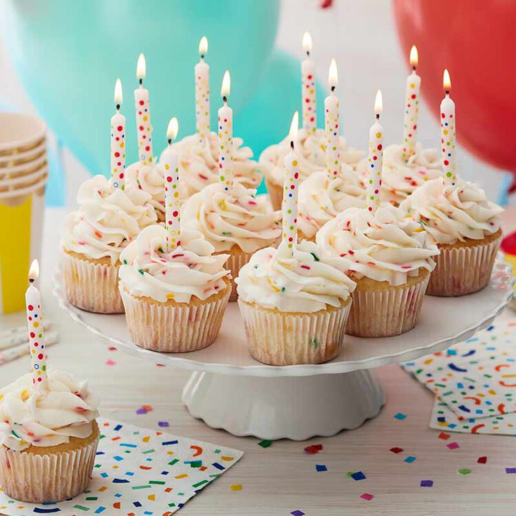 cupcakes frosted with white buttercream frosting and decorated with candles