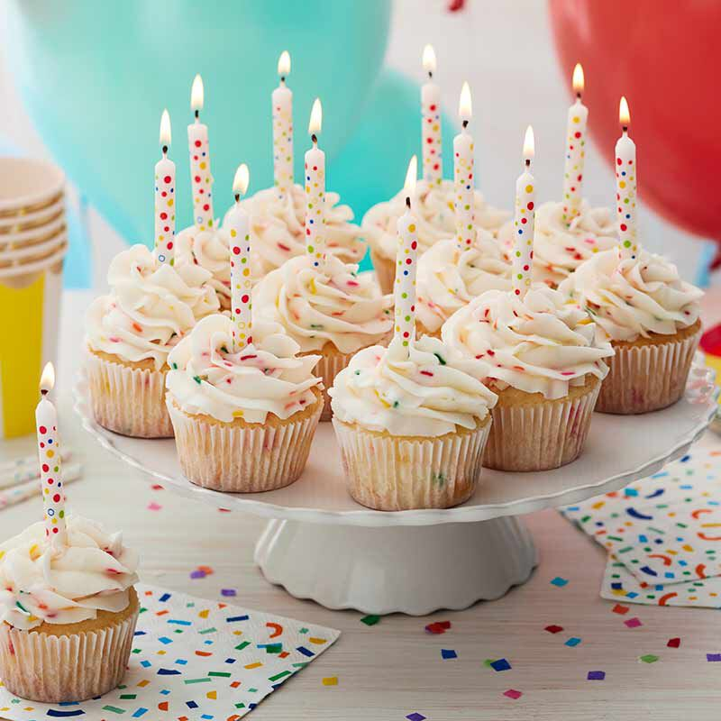 cupcakes frosted with white buttercream frosting and decorated with candles image number 0