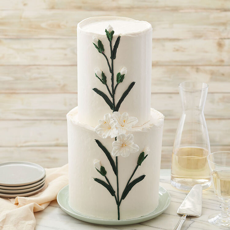Two-tiered white buttercream cake with gladiola flowers and buds