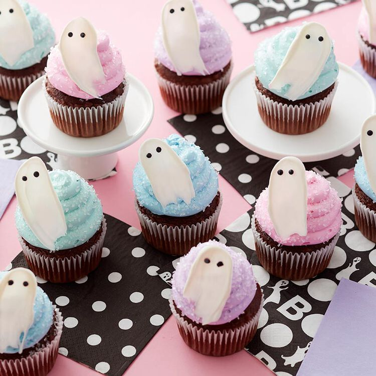Pastel blue, purple, and pink buttercream cupcakes with white Candy Melt ghosts on top