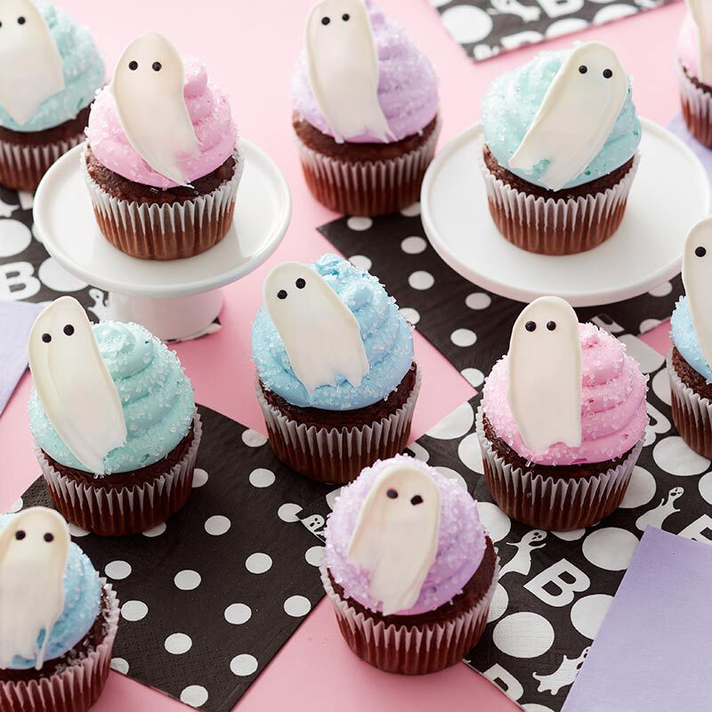 Pastel blue, purple, and pink buttercream cupcakes with white Candy Melt ghosts on top image number 0