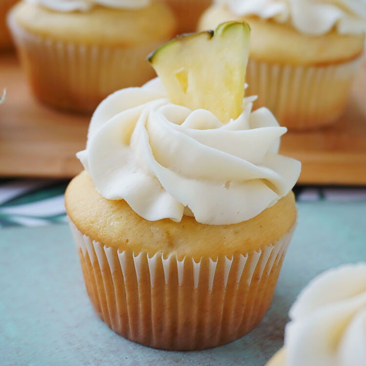 Pineapple Cupcakes with Pineapple Buttercream, topped with a pineapple slice