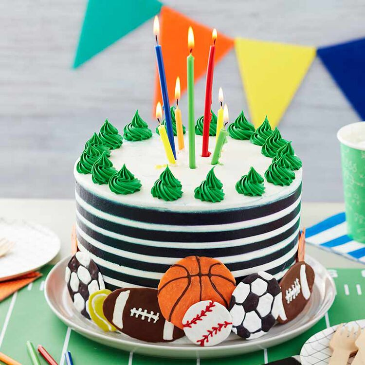 black and white striped buttercream cake with candles and various sports balls