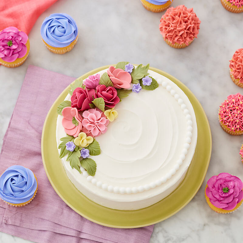 Round, white cake with different types of fondant flowers topping it. image number 0