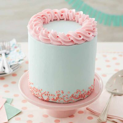 light blue and pink buttercream frosted cake decorated with pink sprinkles and a light pink spiral border