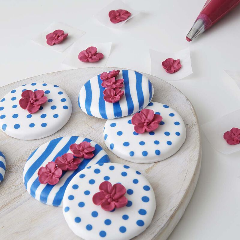 Round cookies with blue and white stripes and white with blue polka dots using royal icing.  Red apple blossoms sit on top.  image number 0