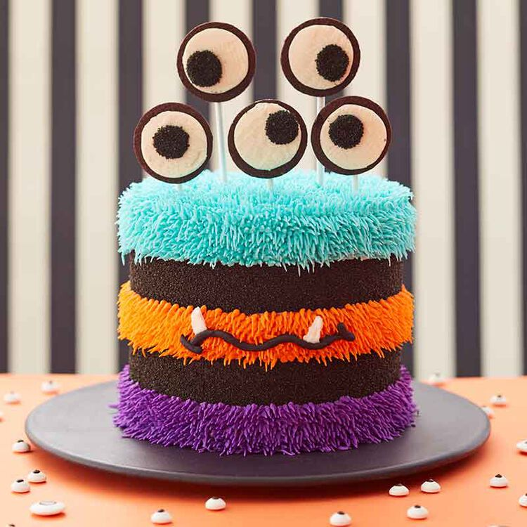 3 tiered cake iced with halloween colors and topped with eyeballs