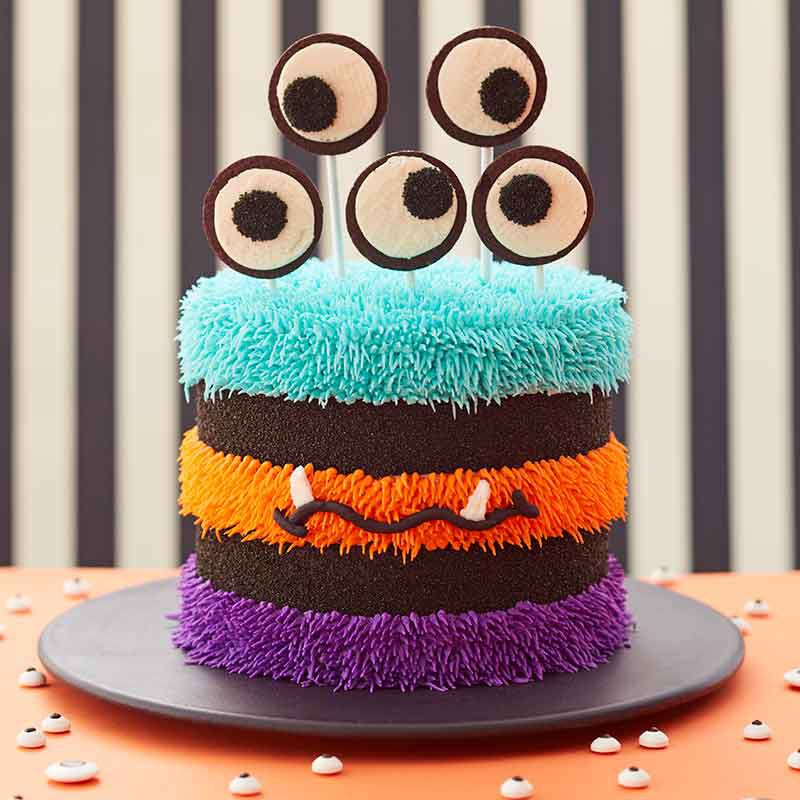 3 tiered cake iced with halloween colors and topped with eyeballs image number 0