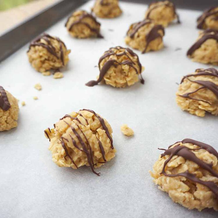 no bake peanut butter cookies with chocolate candy melt drizzle on a cookie sheet