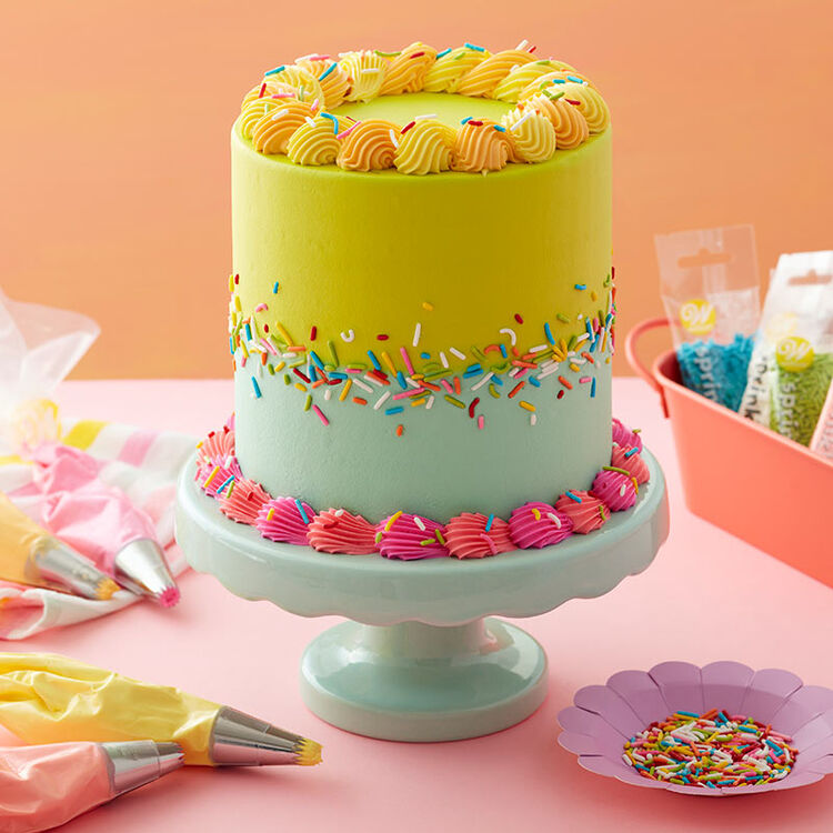 Green, Pink, Yellow, and Blue frosted cake decorated with rainbow jimmy sprinkles