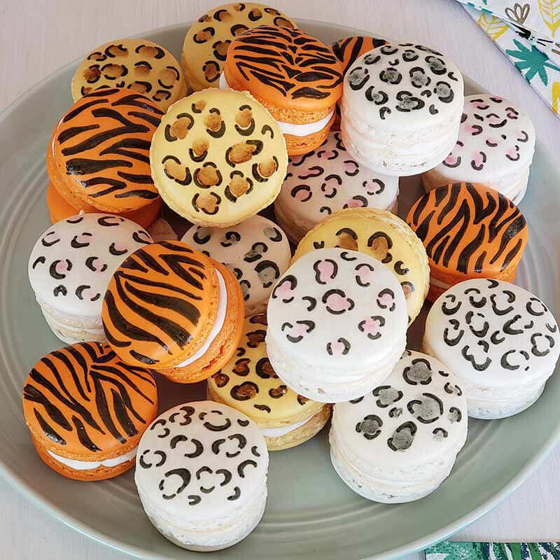 macarons decorated with tiger stripes and grey, pink and white leopard animal print on a plate image number 2