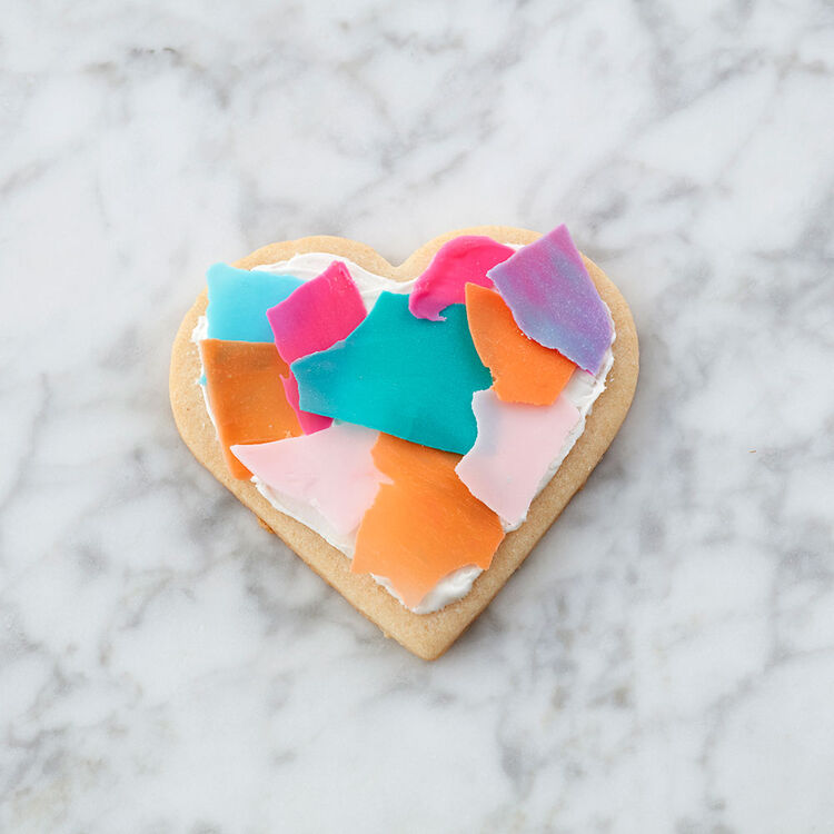 Heart-shaped cookie topped with white icing and broken candy pieces made to look like confetti