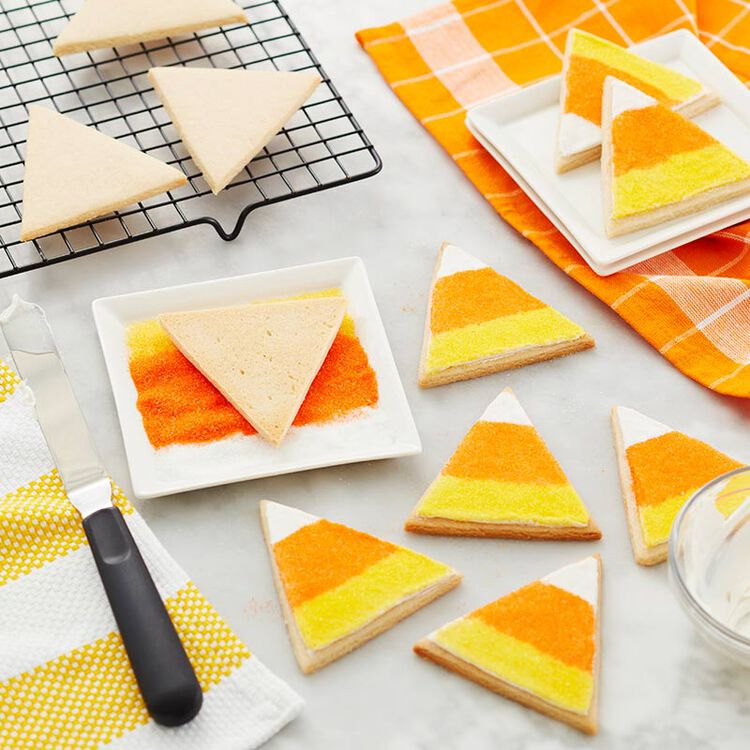 In the process of dipping the triangular sugar cookies into the orange, white, and yellow sugar sprinkles