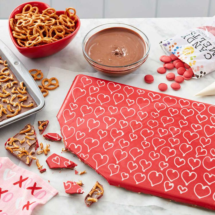 Red, white, and light cocoa Candy Melts are used to make this simple and cute candy bark.  The top is red with white hearts and the chocolate and pretzels are on the bottom.
