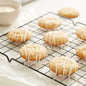 Orange Cream Cookies with a white Candy Melt drizzle on a drying rack