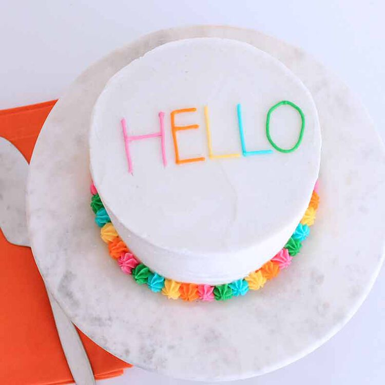 white frosted cake with a colorful piped border and the words hello written in color