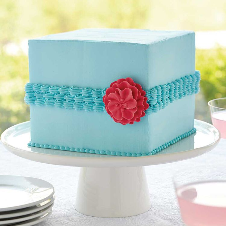 Blue square cake with blue shell border and a red icing rose
