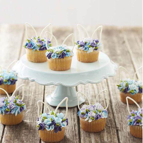 Blue and purple floral piped buttercream cupcakes with white candy easter bunny ears