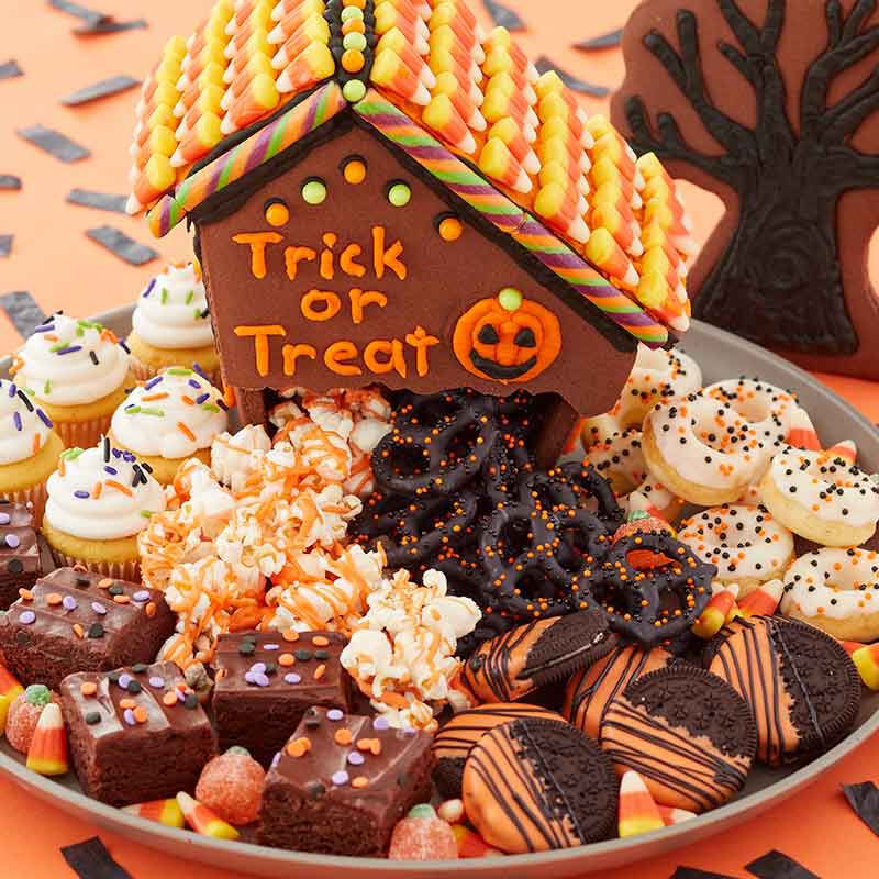 charcuterie board for halloween made with a halloween gingerbread home, candy and halloween treats image number 0