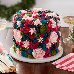 Round cake piped with stars and rosettes in pinks, red, green, and blue buttercream