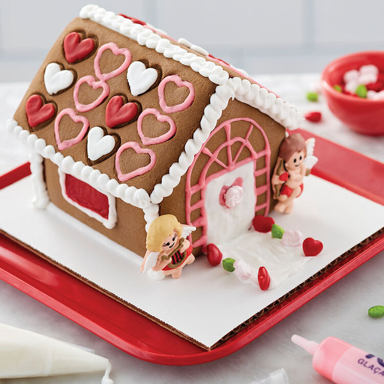 Valentine's Day chocolate cookie house, decorated with red, white, and pink hearts on the roof and cute male and female cupids on either side of the white door with pink heart window